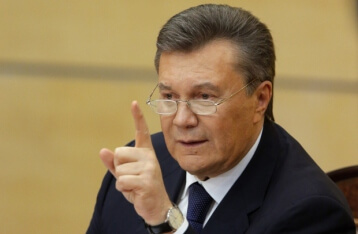 Президент України Віктор Янукович, person, wall, man, human face, indoor, tie, cellphone, clothing, suit, older. Viktor Yanukovych wearing a suit and tie talking on a cell phone