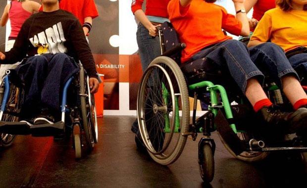 Що роблять в Україні для дітей-інвалідів (ВІДЕО). дітей, person, wheelchair, indoor, wheel, bike, seat. A group of people riding on the back of a bicycle