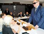 На НСК «Олімпійський» відбувся сеанс одночасної гри чемпіона світу з шахів серед сліпих (ФОТО). інваспорт, сліпих, інвалідів, person, indoor, man, clothing, event, business, dinner, suit, table, restaurant. A group of people standing around a table