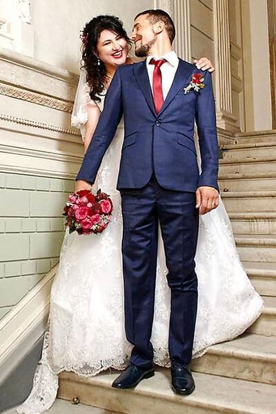 """Виктор Кардаш: """"Перед тем как сделать любимой предложение, я две недели учился на протезе становиться на колено"""". виктор кардаш, person, wedding dress, bride, dress, suit, clothing, wedding, standing, fashion accessory, gown. A person in a suit standing in front of a building"""