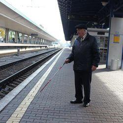 З білим ціпком по вокзалу. незрячих, шрифтом брайля, train, platform, station, person, standing, clothing, man, footwear, sidewalk, subway. A man standing next to a platform at a train station