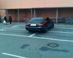 Кабмін схвалив законопроект про збільшення штрафів для водіїв за паркування на місцях осіб з інвалідністю. інвалідністю, road, land vehicle, building, vehicle, car, wheel, outdoor, tire, auto part, vehicle registration plate. A group of people standing in a parking lot