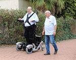 В Ізраїлі створили інвалідний візок, який дозволяє людині вставати (ФОТО, ВІДЕО). переміщуватися, outdoor, ground, tree, person, wheel, clothing, tire, footwear, land vehicle, man. A group of people standing around a motorcycle