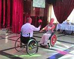 "Вкус жизни: как пара танцует на инвалидных колясках (ВИДЕО). wheelchair dance, виктор карпов, запоріжжя, ирина петровская, відео, инвалидов, особи з інвалідністю, профреабилитация, танец ""сердце"", танцы на инвалидных колясках, фаер-шоу, curtain, floor, indoor, wheelchair, red. A person in a red curtain"