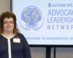 «Организация Autism Speaks во многих вопросах пересмотрела свою политику». autism leadership network, autism speaks, инна сергиенко, аутизм, аутист, clothing, human face, person, woman, suit, smile, posing. A person standing in front of a sign