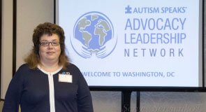 «Организация Autism Speaks во многих вопросах пересмотрела свою политику». autism leadership network, autism speaks, инна сергиенко, аутизм, аутист, clothing, human face, person, woman, suit, smile, posing. A person standing in front of a sign