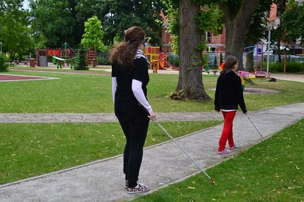 А освіта, справді, для всіх дітей?. діти, навчальні заклади, навчання, інвалідність, інклюзивна освіта, grass, outdoor, tree, footwear, park, clothing, playground, person, woman, trousers. A girl flying a kite in a park