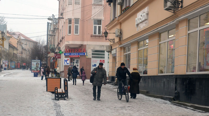 Як фізично обмеженим ужгородцям потрапити до аптек, магазинів, кафе?. ужгород, візочник, доступ, пандус, інвалід, building, outdoor, bicycle, street, person, people, way, scene, clothing, vehicle. A group of people walking on a city street