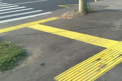 Слепые мариупольцы будут переходить дорогу по тактильной плитке. мариуполь, инвалид, переходы, слабовидящий, тактильная плитка, road, outdoor, street, way, ground, scene, road surface, tarmac, asphalt, yellow. A sign on the side of a road