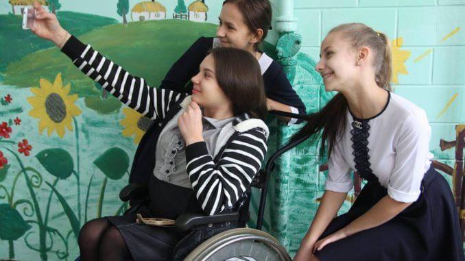 Кропивничани зняли соціальний відеоролик про діток із інвалідністю (ФОТО, ВІДЕО). кропивницький, порушення прав, соціальний відеоролик, інвалід, інвалідність, person, human face, clothing, smile, girl, woman, boy, crowd. A group of people looking at a phone
