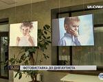 «Єднання світів»: виставку із фото «особливих» дітей відкрили у Сумах (ВІДЕО). наталія кармазіна, суми, аутизм, дитина-інвалід, фотовиставка, human face, screenshot, indoor, person, billboard, picture frame, poster. A sign above a photo of a person