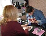 При поддержке USAID 150 переселенцев с инвалидностью нашли новую работу в Донецкой области. usaid, донецкая область, инвалидность, переселенец, трудоустройство, person, indoor, clothing, computer. A group of people sitting at a table