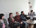 Засідання районного комітету забезпечення доступності інвалідів. знам'янка, доступність, обмеженими фізичними можливостями, соціальне таксі, інвалід, person, clothing, indoor, computer, laptop, wall, man, human face, furniture, table. A group of people sitting at a table