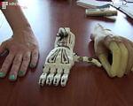У Полтаві відкрили підприємство, яке друкує протези на ЗD принтері (ВІДЕО). зd принтер, полтава, протез, підприємство, стартап, indoor, table, floor, statue, sculpture, skull, wooden, feet. A hand holding a remote control on a wooden table