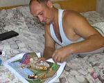 Вишиване диво Андрія Слюсарчука (ВІДЕО). андрій слюсарчук, ковель, виставка, учасник ато, інвалід, person, drawing, painting, indoor, bed, clothing. A person sitting on a bed