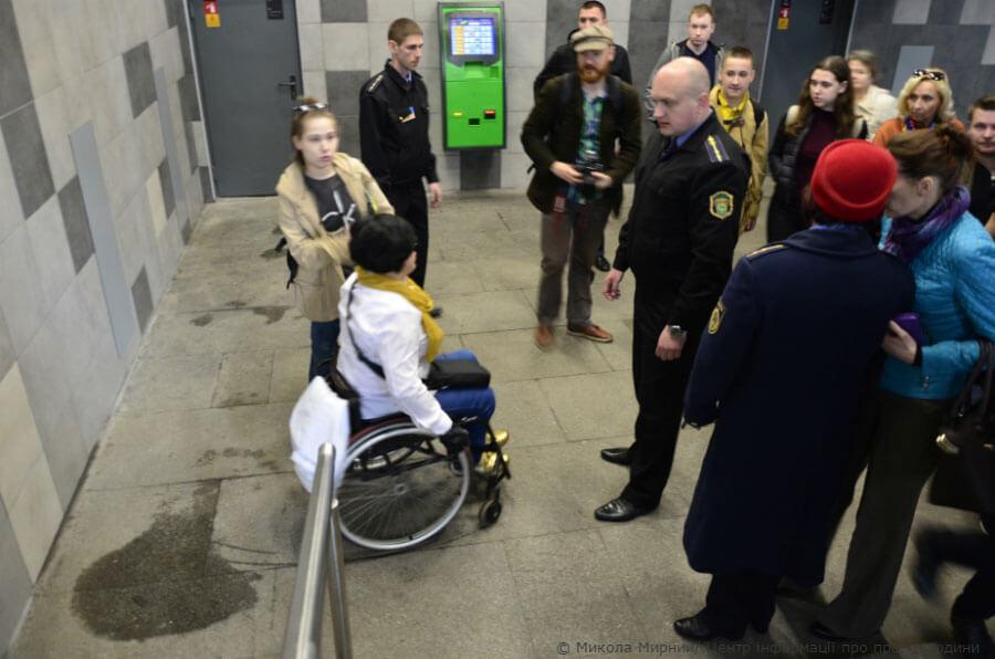 """Кияни на візках показали, що станція метро """"Лівобережна"""" для них недоступна. київ, метрополітен, пандус, підйомник, інвалідність, person, wheelchair, clothing, outdoor, footwear, man, bicycle, crowd. A group of people standing on a sidewalk"""