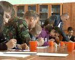 Арт-терапія: військові АТО віддячили за підтримку дітям з особливими потребами (ВІДЕО). суми, арт-терапія, військовий, особливими потребами, інклюзивний клас, table, person, sitting, indoor, human face, clothing, people, man, drink, meal. A group of people sitting at a table