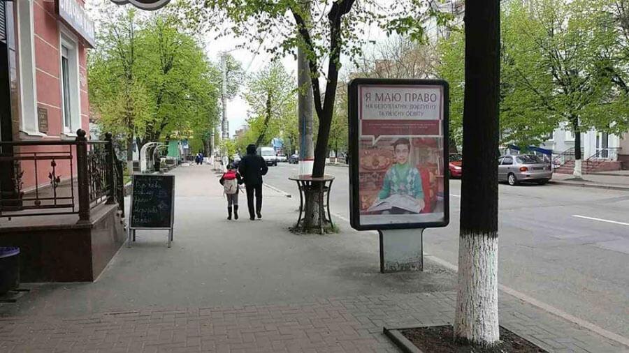 У Кропивницькому з'явилися сіті-лайти за «безбар'єрне середовище» (ФОТО). кропивницький, меседж, сіті-лайт, інвалідність, інформаційна кампанія, outdoor, tree, ground, billboard, person, street, sidewalk, clothing, way, curb. A sign on the side of the street