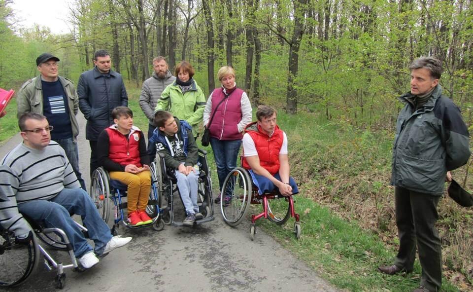 Ужгородці знайомилися з безбар'єрними міськими лісами Кошиць (ФОТО). кошице, ужгород, доступність, обмеженими можливостями, інвалідність, person, tree, outdoor, grass, people, group, bicycle, clothing, wheelchair, park. A group of people in a park