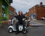 Британский инженер создал реактивный скутер для инвалидов. том бегнелл, дрэг-рейсинг, изобретение, инвалид, реактивный скутер, building, outdoor, road, sky, land vehicle, helmet, wheel, vehicle, person, motorcycle. A man riding a motorcycle on a city street