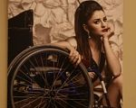 """""""Можемо бути привабливими і успішними"""" – показують виставку з красунями на інвалідному візку (ФОТО). дівчина, красуня, фотовиставка нескорена краса, інвалідний візок, інвалідність, wall, wheel, bicycle, indoor, person, land vehicle, clothing, bicycle wheel, tire, woman. A woman standing in front of a bicycle"""