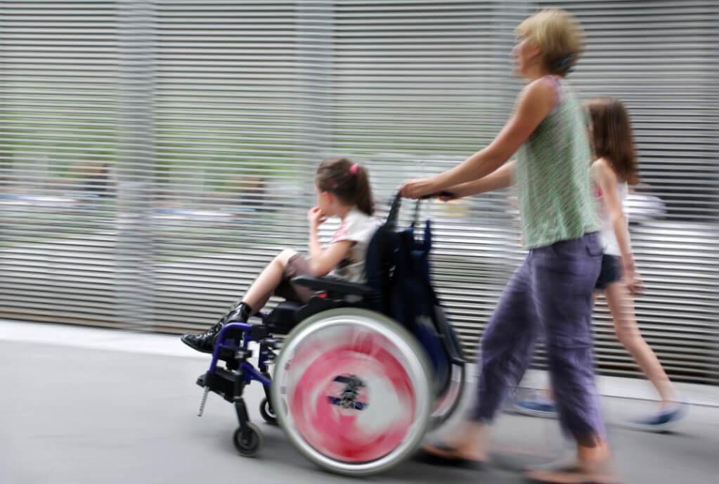 В області впроваджується системний підхід до підтримки дітей з інвалідністю. запорізька область, дитина-інвалід, раннє втручання, тренинг, інвалідність, person, road, window, wheel, riding, clothing, tire, auto part, toddler. A woman riding a bike next to a window