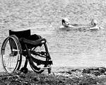 Маріупольці з інвалідністю відкрили пляжний сезон. мариуполь, відпочинок, пляжний сезон, спеціалізований пляж, інвалідність, outdoor, water, ground, beach, black and white, wheel, chair, sand, sea, sandy. A bicycle is parked next to a body of water