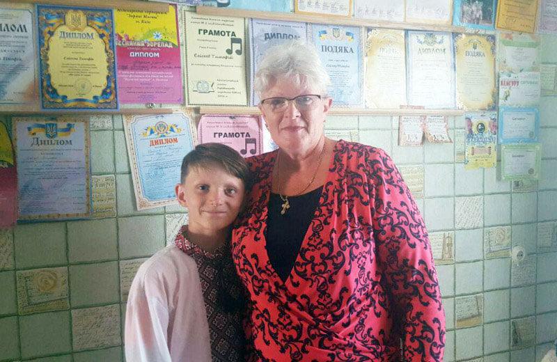 11-річний полтавець з вадами зору, якого виховує бабуся, переміг на міжнародних музичних фестивалях в Болгарії. тимофій єлісєєв, баян, вади зору, обмеженими можливостями, інвалідність, person, human face, clothing, smile, woman, handwriting, shop. A man and a woman standing in front of a store