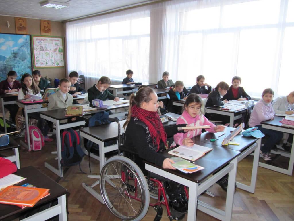 Школа нерівних можливостей. особливими освітніми потребами, соціалізація, інвалідність, інклюзивна освіта, інклюзія, indoor, table, floor, person, group, furniture, people, clothing, chair, computer. A group of people sitting at a table