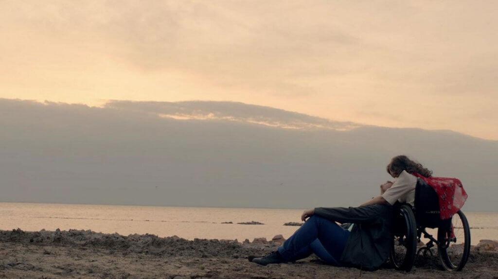 Модель-радниця Філатова знялася у кліпі відомого українського гурту (ВІДЕО). олександра кутас, гурт скай, кліп, модель, обмеженими фізичними можливостями, outdoor, sky, beach, cloud, water, ocean, sunset, nature, shore, sunrise. A man sitting on a beach