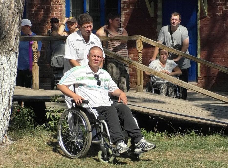 У Чернігові відкрився комплексний центр для людей з інвалідністю (ВІДЕО). го інтеграція, чернігів, комплексний центр, інвалід, інвалідність, person, grass, outdoor, clothing, man, wheelchair, smile, footwear. A group of people sitting on a bench