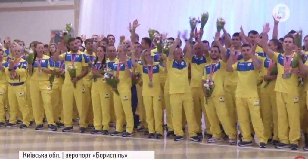 """Дзвін золота та сюрпризи: як в """"Борисполі"""" зустрічали українську переможну збірну (ВІДЕО). дефлімпіада, спортсмен, сюрприз, інвалід, інвалідність, person, posing, clothing, group, dance, smile, row, lined, footwear, woman. A group of people posing for a photo"""