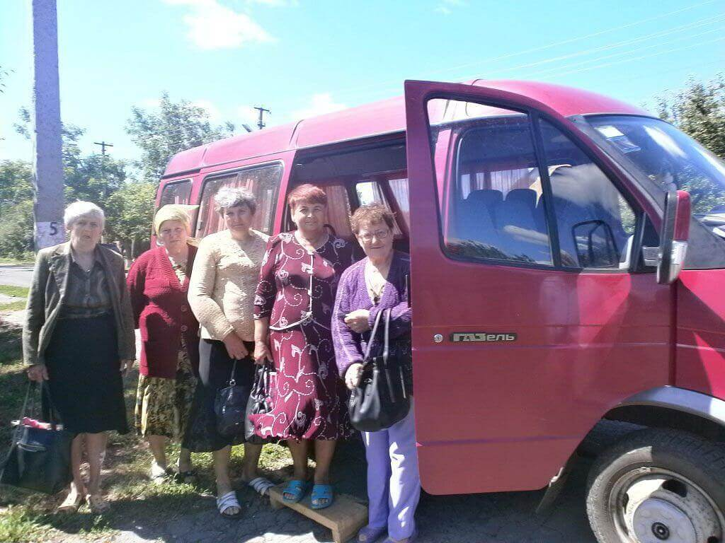 У Шишацькій громаді працює соціальне таксі для людей з особливими потребами та одиноких. шишаки, особливими потребами, пенсіонер, соціальне таксі, інвалід-візочник, sky, outdoor, bus, person, land vehicle, vehicle, transport, standing, clothing, van. A group of people standing in front of a bus
