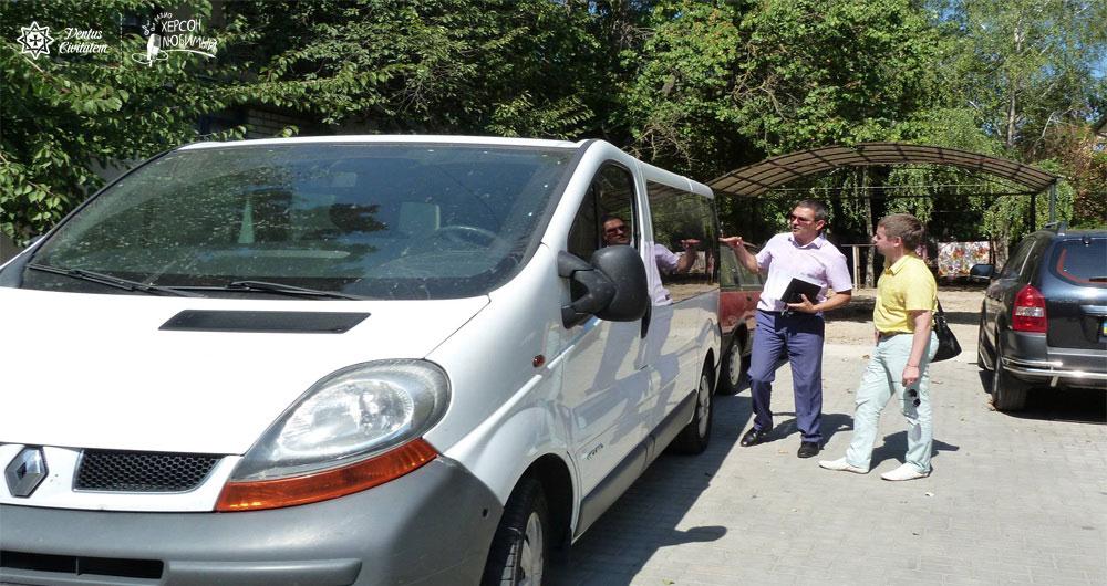 В Херсоне появился первый автомобиль новой службы «Социальное такси». херсон, инвалидность, ограниченными возможностями, социальное такси, інвалід, car, tree, outdoor, road, land vehicle, vehicle, wheel, parking, van, auto part. A man in a police car parked in a parking lot