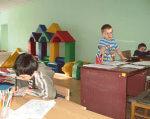 С особенными детьми занимаются индивидуально. славянск, инвалид, индивидуальные уроки, особенными потребностями, учебный процесс, child, indoor, person, boy, wall, baby, little, young, clothing, child art. A little boy sitting at a table