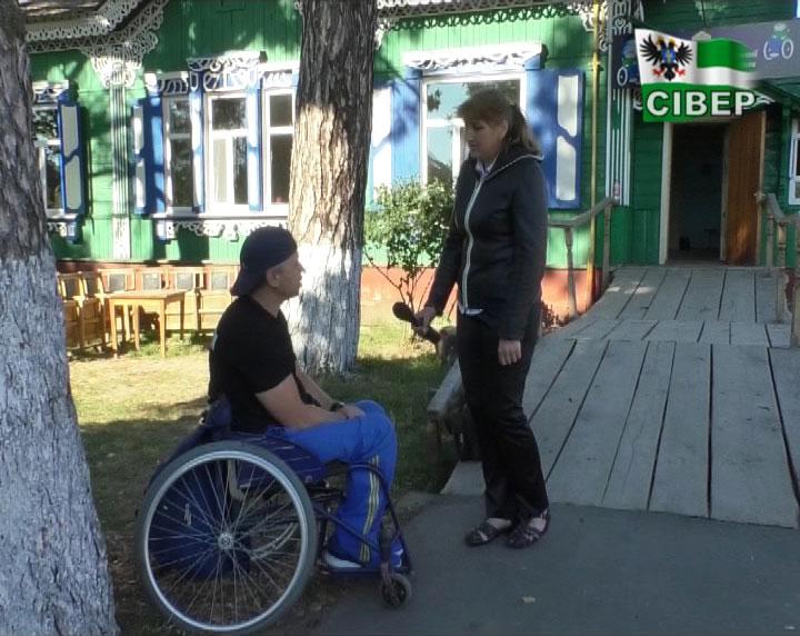 На візку з Чернігова в Сновськ (ВІДЕО). сергій шурута, чернігівщина, велопробіг, спинальник-візочник, інвалідність, outdoor, ground, person, wheelchair, clothing, sidewalk, wheel, man, footwear, bicycle. A person standing on a sidewalk