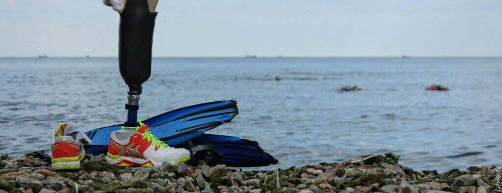 Приключения итальянцев под «Россией»: как водолазы из Ливорно учили одесситов с инвалидностью дайвингу (ФОТО). одесса, водолаз, дайвинг, инвалид, инвалидность, water, sky, outdoor, beach, sea, ocean, shore. A boat sitting on top of a beach next to a body of water