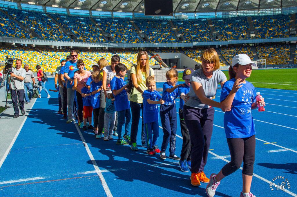 Пресс-релиз: 60 детей с аутизмом проекта Kids Autism Games будут заниматься спортом. киев, нск «олимпийский», аутизм, проект kids autism games, тренировка, person, clothing, sports uniform, footwear, stadium, group, fan, line. A group of people on a court