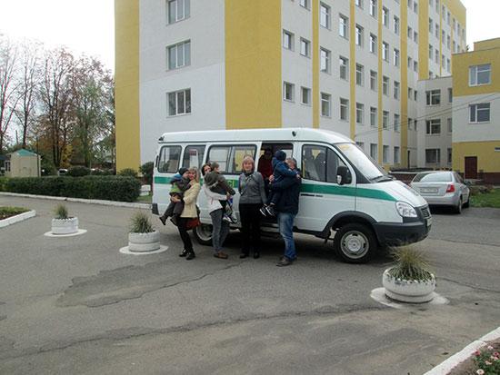 Для діток-інвалідів – «Соціальне таксі». лубни, обмеженими фізичними можливостями, соціальне таксі, транспортна послуга, інвалід, outdoor, road, land vehicle, vehicle, van, car, person, wheel. A group of people walking down a street next to a car