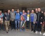 Українці зустріли ветеранів АТО, які повернулися після участі у Марафоні морської піхоти США (ВІДЕО). марафон морської піхоти сша, ампутация, ветеран ато, поранення, інвалідність, person, ceiling, posing, clothing, smile, man, standing, group, indoor, jeans. A group of people posing for a photo