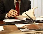Спрощено доступ особам з обмеженими можливостями до професії адвоката. адвокат, кваліфікаційний іспит, професія, пільгова умова, інвалід, person, table, indoor, man, bottle, suit, dish, drink, working, document. A man in a suit sitting at a table using a laptop