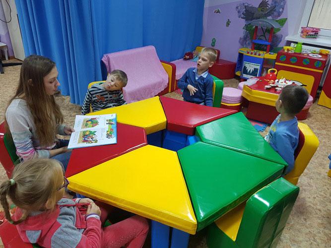 У Ковельському центрі соціальної реабілітації дітей-інвалідів застосовують особливі методи терапії. ковель, адаптація, дитина-інвалід, особливими потребами, соціалізація, person, table, indoor, child, toy, furniture, chair, cartoon. A group of people sitting at a table