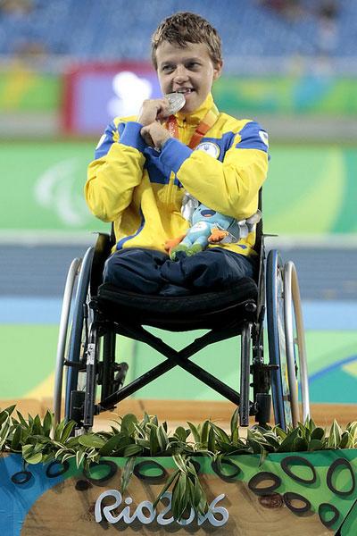 Зоя Овсий: «Специального метательного снаряда — клаба — у меня не было, я тренировалась с кухонной скалкой». зоя овсій, паралимпиада, артрогрипоз, инвалид, спортсменка, outdoor, person, clothing, wheelchair, seat. A person sitting on a bench
