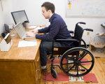 Реалии рынка труда Херсона: где может трудоустроиться человек с ограниченными физическими возможностями?. херсон, вакансія, инвалидность, работодатель, трудоустройство, floor, person, indoor, furniture, desk, table, computer, wheelchair, chair. A man sitting at a table using a laptop