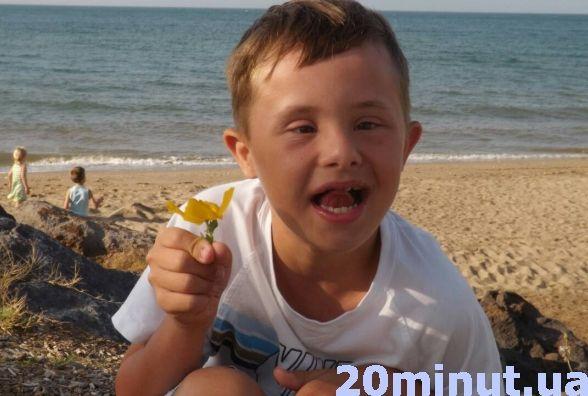 "Тернополянка змирилася з діагнозом сина і радіє життю. ""сонячна"" дитина, діагноз, помічник, синдром дауна, інвалід, person, outdoor, water, sky, toddler, beach, boy, child, baby, human face. A boy drinking water from a beach"