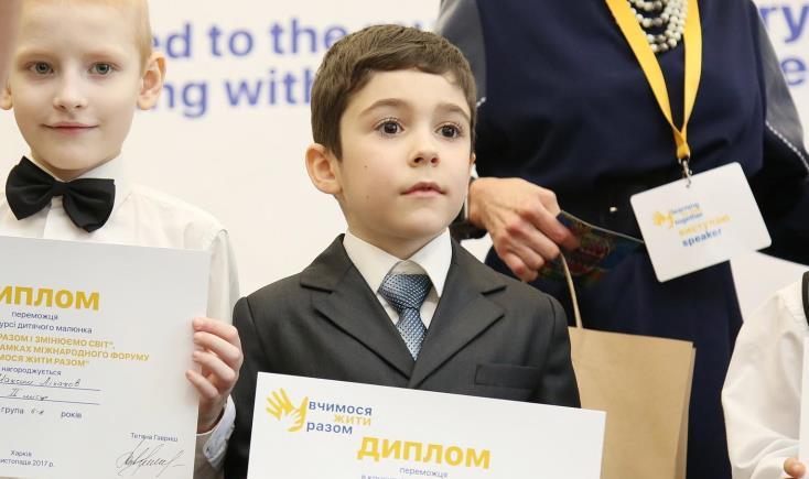 «Бути нетолерантними сьогодні вже ненормально». харків, форум, інвалідність, інклюзивна освіта, інтеграція, person, suit, human face, clothing, tie, necktie, posing, dressed. A small boy is holding a sign