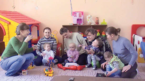 В Харькове родителей малышей с инвалидностью научат не стесняться своих детей. харьков, заболевание, инвалидность, помощь, раннее вмешательство, toddler, baby, person, child, sitting, indoor, family, boy, clothing, human face. A group of people sitting at a table