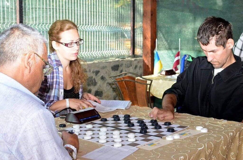 «Чого слину пускаєш?» — казали хворому на ДЦП, а він… став чемпіоном світу!. дцп, сашко гонгальський, чемпіон світу, шашки, інвалідність, person, man, indoor, laptop, glasses, clothing, table, board game, human face. A man sitting at a table looking at a laptop