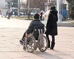 Чи користуються пільгами рівняни, які мають інвалідність? (ВІДЕО). рівне, виплата, громадський транспорт, пільга, інвалідність, outdoor, ground, wheel, person, wheelchair, street, sidewalk, land vehicle, cart, square. A person standing on a sidewalk