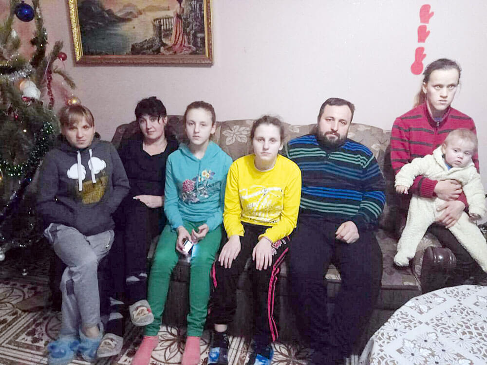 Щастя бути батьками «важких» дітей. прийомна сім'я, сирота, усиновлення, інвалідність, інтернат, person, smile, clothing, human face, wall, indoor, family, posing, group, man. A group of people posing for a photo